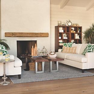 Immagine di un soggiorno tropicale di medie dimensioni e chiuso con pareti bianche, pavimento in legno massello medio, camino classico, nessuna TV e cornice del camino in intonaco