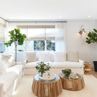 Photo of a large transitional open concept living room in Sydney with white walls, a wall-mounted tv and beige floor.