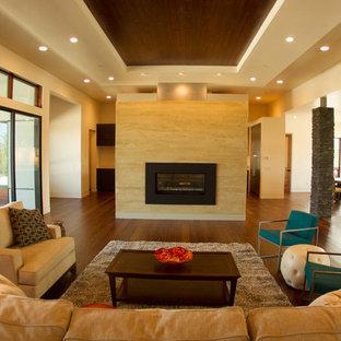 サンルイスオビスポの広いコンテンポラリースタイルのおしゃれなLDK (ベージュの壁、竹フローリング、両方向型暖炉、漆喰の暖炉まわり、壁掛け型テレビ) の写真