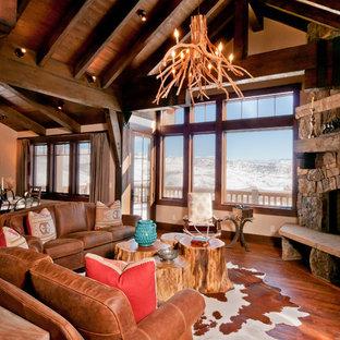 Réalisation d'un salon chalet ouvert et de taille moyenne avec un mur beige, un sol en bois brun, une cheminée d'angle, un manteau de cheminée en pierre, une salle de réception et un téléviseur dissimulé.