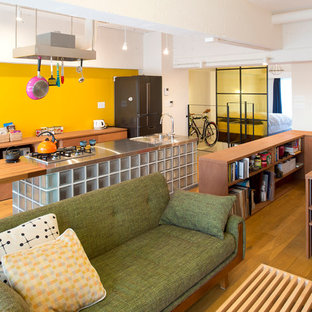Modelo de salón abierto, actual, con paredes amarillas y suelo de madera en tonos medios