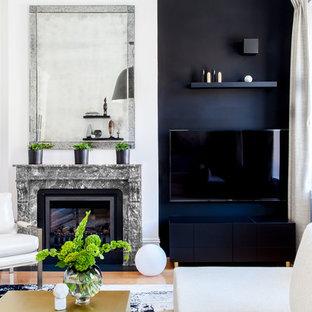 ニューヨークの大きいモダンスタイルのおしゃれな独立型リビング (フォーマル、黒い壁、無垢フローリング、標準型暖炉、石材の暖炉まわり、壁掛け型テレビ) の写真