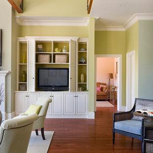 Foto di un grande soggiorno tradizionale aperto con pareti verdi, camino classico, TV nascosta, pavimento in legno massello medio e cornice del camino in legno