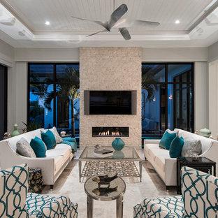 Klassisk inredning av ett mellanstort allrum med öppen planlösning, med grå väggar, travertin golv, en bred öppen spis, en spiselkrans i sten och en väggmonterad TV