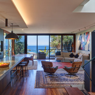 Inspiration for a tropical open concept living room in Sydney with blue walls, dark hardwood floors and brown floor.