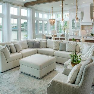 Modelo de salón abierto, costero, con paredes grises, suelo de madera en tonos medios y suelo marrón