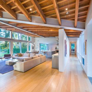 Idee per un grande soggiorno contemporaneo aperto con pareti bianche, parquet chiaro, angolo bar, camino classico, cornice del camino piastrellata e pavimento beige