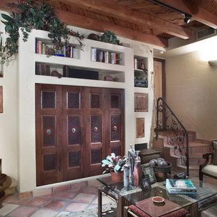 Exemple d'un salon avec une bibliothèque ou un coin lecture sud-ouest américain avec un mur blanc et un sol en carreau de terre cuite.