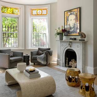 Modelo de salón para visitas abierto, clásico renovado, grande, sin televisor, con paredes grises, suelo de madera en tonos medios y chimenea tradicional
