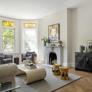 Diseño de salón para visitas abierto, clásico, sin televisor, con paredes grises, suelo de madera en tonos medios y chimenea tradicional