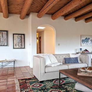 Imagen de salón abierto, de estilo americano, de tamaño medio, sin televisor, con paredes blancas, suelo de baldosas de terracota, chimenea tradicional, marco de chimenea de yeso y suelo naranja