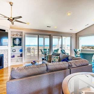 他の地域の中サイズのビーチスタイルのおしゃれなLDK (フォーマル、ベージュの壁、無垢フローリング、コーナー設置型暖炉、タイルの暖炉まわり、壁掛け型テレビ) の写真