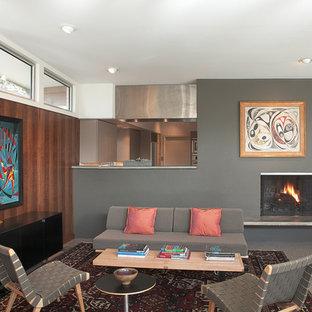 Foto di un grande soggiorno minimalista aperto con sala formale, pareti grigie, pavimento in cemento, camino classico, cornice del camino in metallo e nessuna TV