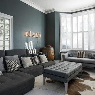 Réalisation d'un grand salon tradition ouvert avec un mur gris et un téléviseur fixé au mur.