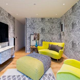 ロンドンの中くらいのコンテンポラリースタイルのおしゃれな独立型リビング (グレーの壁、淡色無垢フローリング、壁掛け型テレビ、ベージュの床、壁紙) の写真