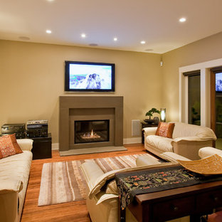 Example of a mid-sized trendy enclosed medium tone wood floor living room design in Vancouver with beige walls, a standard fireplace, a concrete fireplace and a wall-mounted tv