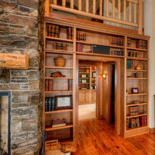 Ispirazione per un soggiorno country di medie dimensioni e aperto con libreria, pavimento in legno massello medio, camino classico, cornice del camino in pietra e pavimento marrone