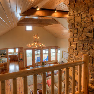 Inspiration for a mid-sized country loft-style carpeted and beige floor living room remodel in Seattle with beige walls, a standard fireplace and a stone fireplace