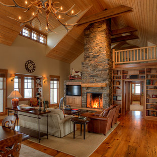 Example of a mid-sized cottage open concept medium tone wood floor and brown floor living room design in Seattle with a standard fireplace, a stone fireplace, a media wall and beige walls