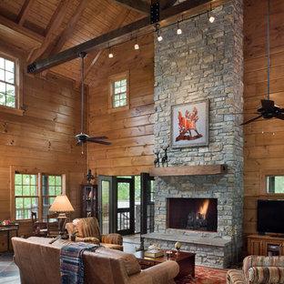 ナッシュビルの広いラスティックスタイルのおしゃれなリビング (茶色い壁、スレートの床、石材の暖炉まわり、コーナー型テレビ) の写真