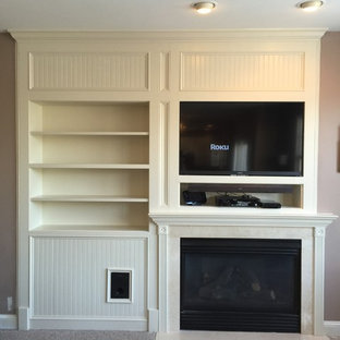 This is an example of a small traditional living room in Baltimore with a library, beige walls, carpet, a standard fireplace, a stone fireplace surround and a built-in media wall.