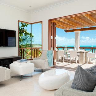 Ejemplo de salón tropical con paredes blancas y televisor colgado en la pared