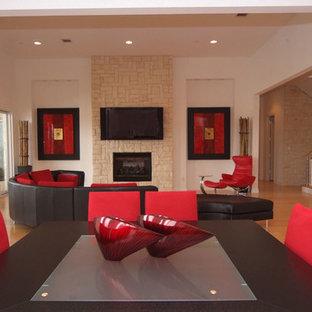Foto de salón para visitas abierto, minimalista, grande, con paredes beige, suelo de madera clara, chimenea tradicional, marco de chimenea de piedra y televisor colgado en la pared
