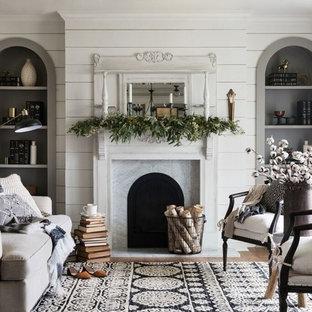 Inspiration pour un salon style shabby chic de taille moyenne et ouvert avec une salle de réception, un mur blanc, un sol en bois brun et une cheminée standard.