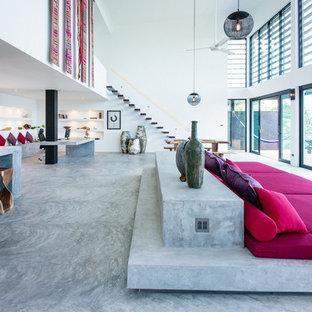 Esempio di un grande soggiorno minimal aperto con sala formale, pareti bianche, pavimento in cemento, camino ad angolo, cornice del camino in cemento, parete attrezzata e pavimento grigio