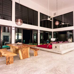 他の地域の大きいビーチスタイルのおしゃれなLDK (フォーマル、白い壁、コンクリートの床、コーナー設置型暖炉、コンクリートの暖炉まわり、埋込式メディアウォール、グレーの床) の写真
