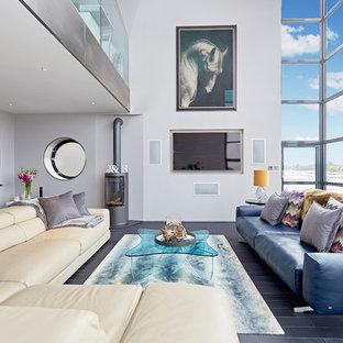 Idee per un grande soggiorno design stile loft con pareti grigie, stufa a legna, parete attrezzata e pavimento nero