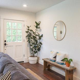ポートランドの小さいカントリー風おしゃれなLDK (白い壁、無垢フローリング、標準型暖炉、レンガの暖炉まわり、壁掛け型テレビ、茶色い床) の写真