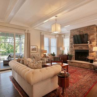 Immagine di un soggiorno stile americano di medie dimensioni e aperto con pareti beige, parquet scuro, camino classico, cornice del camino in pietra e TV a parete