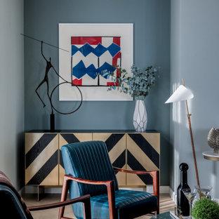Foto på ett stort funkis allrum med öppen planlösning, med blå väggar, ljust trägolv, en dubbelsidig öppen spis, en spiselkrans i metall, en inbyggd mediavägg och grått golv