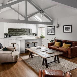 Diseño de salón abierto, campestre, grande, con paredes blancas, suelo de madera en tonos medios, estufa de leña, televisor independiente y suelo marrón