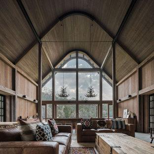 Réalisation d'un salon chalet de taille moyenne et ouvert avec un sol en ardoise, une cheminée standard, un manteau de cheminée en pierre, un sol gris et un mur marron.