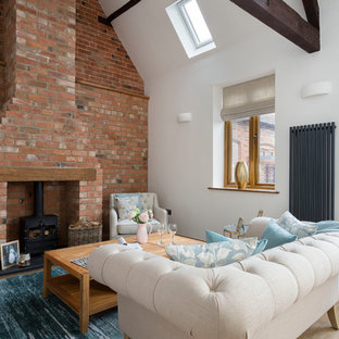 Photo of a rural living room in West Midlands with white walls, light hardwood flooring, a wood burning stove, a brick fireplace surround and beige floors.