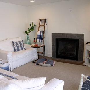 他の地域の中サイズのビーチスタイルのおしゃれなLDK (白い壁、淡色無垢フローリング、標準型暖炉、コンクリートの暖炉まわり、壁掛け型テレビ) の写真