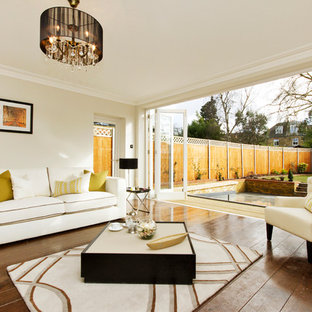 Inspiration for a traditional open plan living room in London with beige walls and medium hardwood flooring.