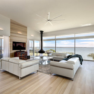 Contemporary open concept living room in Adelaide with white walls, light hardwood floors, a hanging fireplace, a wall-mounted tv and beige floor.