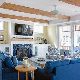他の地域のビーチスタイルのおしゃれなリビング (黄色い壁、無垢フローリング、標準型暖炉、タイルの暖炉まわり、壁掛け型テレビ、茶色い床) の写真