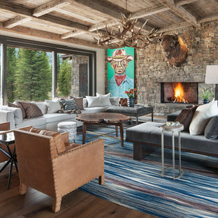 Living room - large rustic open concept medium tone wood floor and brown floor living room idea in Other with a standard fireplace, a stone fireplace and white walls