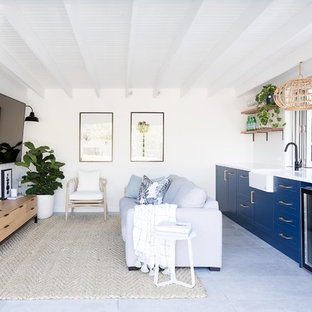 Photo of a small beach style open concept living room in Sydney with white walls, a wall-mounted tv and grey floor.