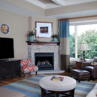 ミルウォーキーのトラディショナルスタイルのおしゃれなLDK (ベージュの壁、無垢フローリング、コーナー設置型暖炉、石材の暖炉まわり、据え置き型テレビ) の写真