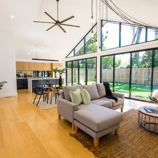 Photo of a large contemporary open concept living room in Brisbane with white walls, light hardwood floors and brown floor.