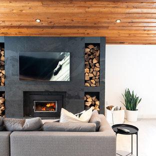 Foto di un soggiorno minimal con pavimento in cemento, stufa a legna, pareti bianche, cornice del camino piastrellata, TV a parete e pavimento bianco