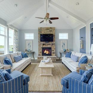 他の地域のビーチスタイルのおしゃれなリビングロフト (青い壁、無垢フローリング、標準型暖炉、石材の暖炉まわり、壁掛け型テレビ) の写真