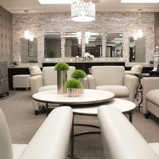 Esempio di un grande soggiorno classico aperto con pareti grigie, pavimento in pietra calcarea e TV a parete