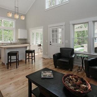 Cette image montre un salon craftsman ouvert avec un mur gris et un sol en bois clair.