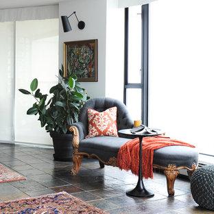 Ejemplo de salón abierto, tradicional renovado, pequeño, sin chimenea, con paredes blancas, suelo de pizarra y televisor colgado en la pared